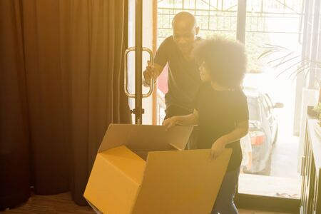 African American family moving into the new house and each holding a box