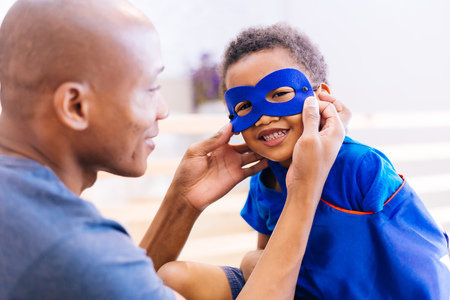 Happy smiling African American son being supported and helped by supportive father for little adventure and protection Stock Photo - 105389077
