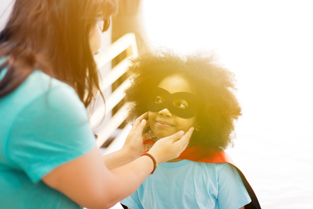 African American kid being supported and helped by supportive mother for little adventure and protection Stock Photo - 105389078