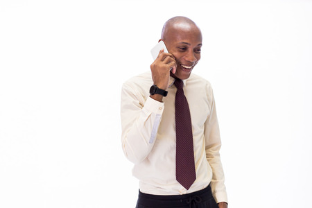 Excited and Happy African American man wearing a shirt and a tie talking on the phone, overwhelming with good news and happiness Stock Photo