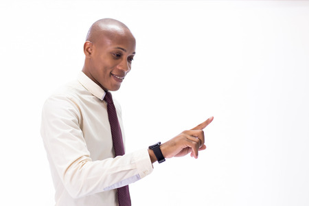 Attractive African American man wearing formal wear with tie, touching a virtual screen. It can be used for layout in touch screen related words and objects.