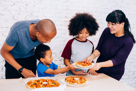 Happy family of African American parents and little boy and girl having pizza together happily at home. Family and parenthood concept Banco de Imagens