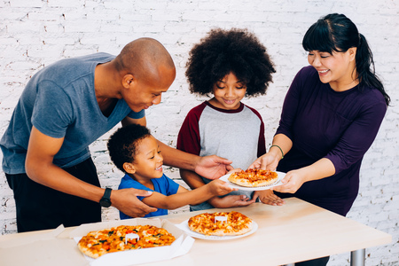 Happy family of African American parents and little boy and girl having pizza together happily at home. Family and parenthood concept Stock Photo