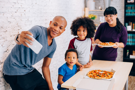 Happy parents and little boy and girl having a meal and taking selfie by smartphone at home. Family and parenthood concept