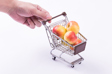 A shopping cart with fruits inside with hands pushing the cart isolated over white background Stock Photo