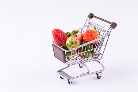 A shopping cart with strawberries inside isolated over white background Stock Photo