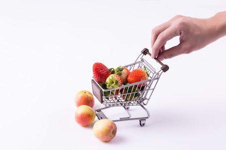 A shopping cart with strawberries inside with hands pushing the cart isolated over white background