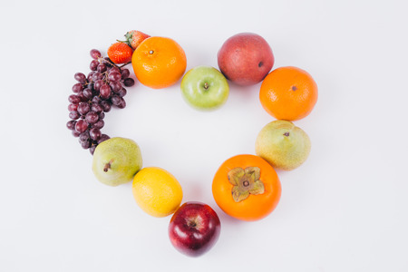 A variety of colorful fruits formed in heart shape in white background, healthy and organic food concept Imagens