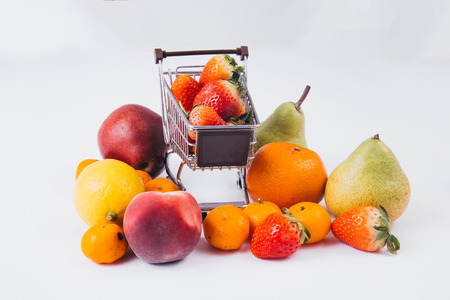 A shopping cart full of various kinds of fruits and groceries isolated over white background