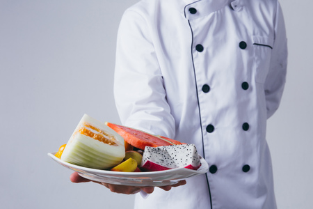 Chef presenting a plate of fruit slices isolated over white background
