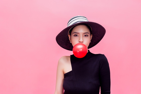 Young sweet and attractive woman in luxury fashion lifestyle blowing chewing bubblegum isolated over pink background