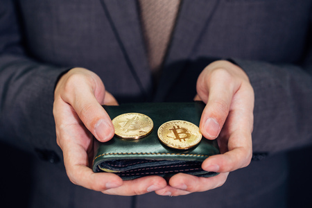 Close-up of businessman with wallet receiving and paying by bitcoin or cryptocurrency - crypto currency is the future of digital cashless financial banking trade Banco de Imagens
