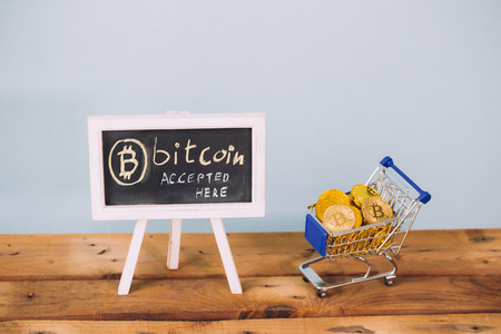 Virtual currency Bitcoin accepted here sign and shopping cart full of bitcoin coins on wooden platform over pastel blue background