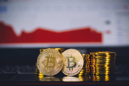 Bitcoin coins pile and two bit coins sitting in front with market crashing and turning red graph chart digital background. Concept of Bitcoin and virtual currency and blockchain technology