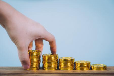 Mannelijke hand die gouden muntstukkenstapel over blauwe pastelkleurachtergrond zetten met exemplaarruimte. Zakelijke groei en geldbesparende concept