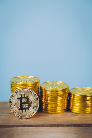Bitcoin coins stack over blue pastel background with copy space. Digital money saving and cryptocurrency concept