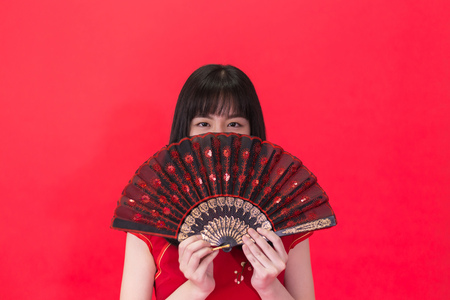 Young Asian woman holding a Chinese traditional style fan isolated over red background. Chinese new year and Spring festival concept can be applied.
