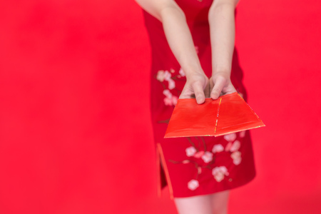 Young Asian woman in Qi Pao giving Ang Pao or Hong Pao or Red Envelope during Chinese New Year isolated over red background