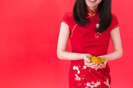 Young new generation Asian woman in Qi Pao holding a bunch of coins - representing wealth and rich business in China concept