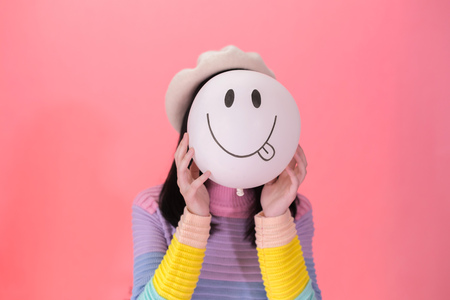 Young woman in colorful fashionable style holding a positive and lively emotion of balloon - joyful and cheerful expression Archivio Fotografico