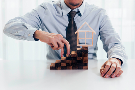 Close up of businessman using hand to climb up a stack of blocks towards house model as dreams of owning real estate or house. Concept of buying, mortgage, loan, business finance and real estate Stok Fotoğraf - 98698856