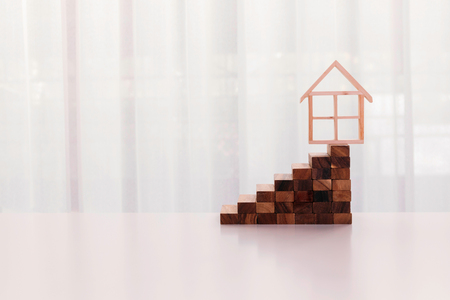 House model on top of slack of stairs isolated over white background - Conceptual of buying and house should be on top of priority