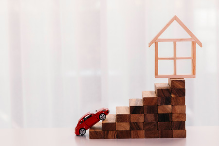 Toy car driving up towards the stairs of achievement with house on the top - big dream and growth achievement in buying house and property