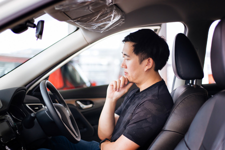 Young Asian man as a customer sitting inside a car thinking and considering to buy automobile or car insurance