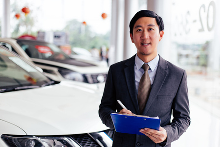 Young Asian business salesman holding a notepad to welcome clients into car showroom Stock Photo
