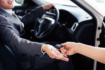 Smiling and happy man receiving a car key from car dealer salesman - car rental and sales concept