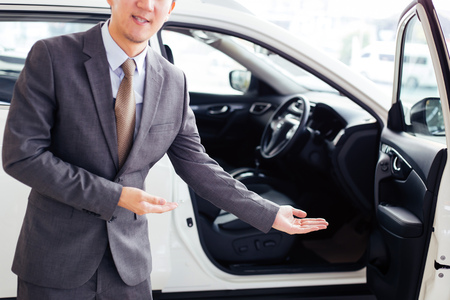 Young chauffeur in business suit welcoming rich and wealthy client on board - rich lifestyle taxi car transportation concept Foto de archivo