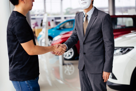 Dishonest and evil salesman in business suit in car dealership company handshaking welcome customers to exploit and deceive customers - fraud and bad quality service in business concept