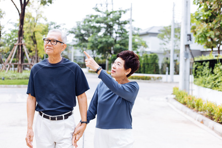 Senior Asian couple walking in the park of residential house