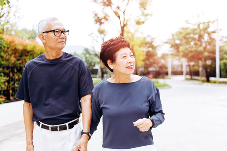 Senior Asian couple walking in the park of residential house. Warm tone with sunlight