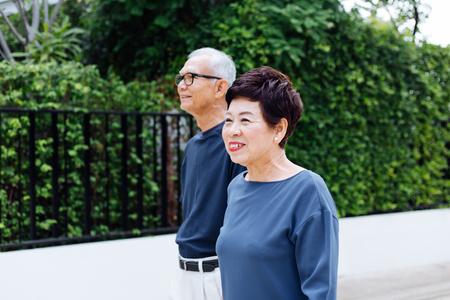 Senior Asian couple walking in the park of residential house