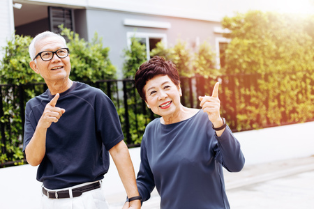 Happy senior Asian couple walking and pointing in outdoor park and house. Warm tone with sunlight