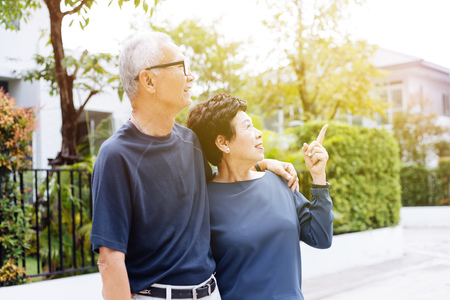 Happy senior Asian couple walking and pointing in outdoor park and house Banque d'images