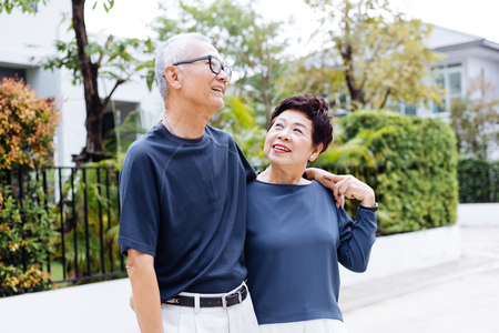 Happy retired senior Asian couple walking and looking at each other with romance in outdoor park and house in background Foto de archivo
