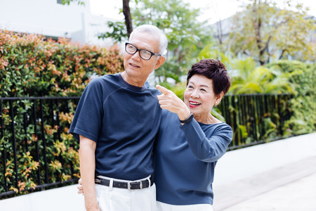 Happy senior Asian couple walking and pointing in outdoor park and house 스톡 콘텐츠