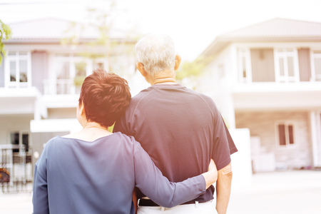 Glückliches älteres Paar von hinten, das vor Haus und Auto schaut. Warmer Ton mit Sonnenlicht Standard-Bild