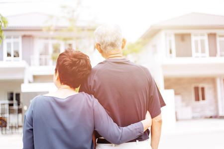 Heureux couple de personnes âgées par derrière regardant devant la maison et la voiture. Ton chaud avec la lumière du soleil Banque d'images