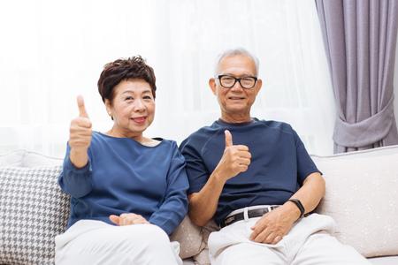Senior Aziatische paar camera kijken en duimen opgevend zittend op de bank thuis Stockfoto