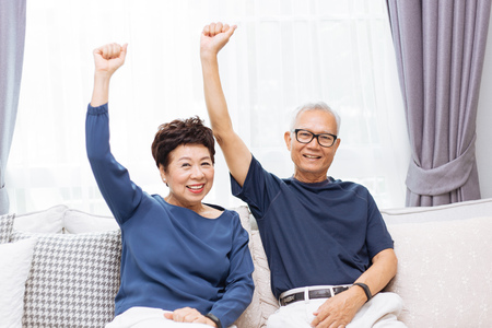 Senior Asian couple looking at camera and raising hands up while sitting on sofa at home Stock Photo