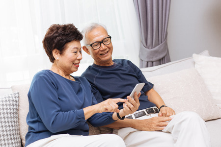 Ältere asiatische Paargroßeltern, die ein Smartphone zusammen auf Sofa zu Hause verwenden