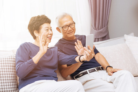 Senior Asian couple grand parents making a video call and waving at the caller Banque d'images