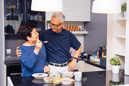 Hogere Aziatische paargrootouders die samen koken terwijl de vrouw voedsel aan de mens voedt bij de keuken. Langdurig relatieconcept
