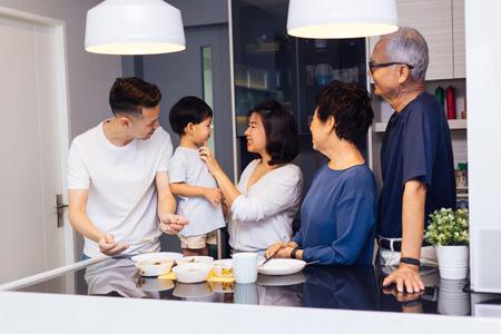 Heureuse famille élargie asiatique préparant la nourriture à la maison pleine de rire et de bonheur