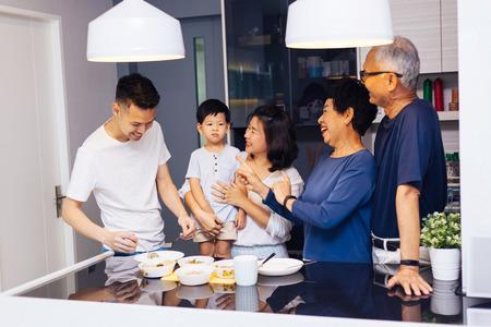 Feliz familia extendida asiática preparando comida en casa llena de risas y felicidad Foto de archivo
