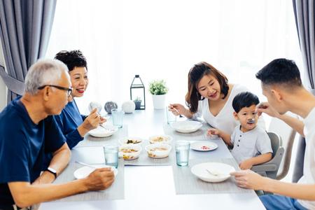 Gelukkige Aziatische uitgebreide familie met diner thuis vol gelach en geluk