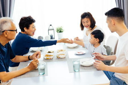 Happy Asian extended family having dinner at home full of laughter and happiness Banco de Imagens - 100933668